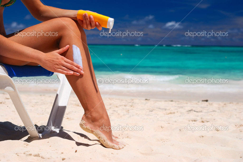 Tan woman applying sun protection lotion — Stock Photo #1537738
