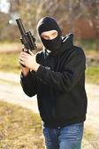 Gunman in black mask holding gun with silencer — Stock Photo