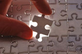 Hand placing missing puzzle piece — Stock Photo