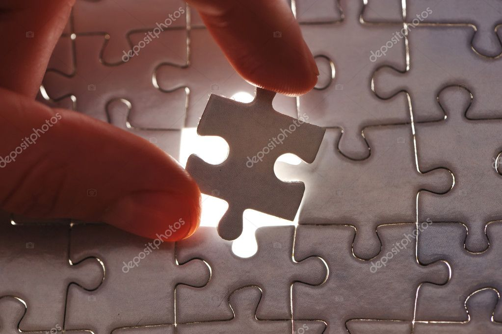 Hand placing missing puzzle piece with shallow DOF — Stock Photo #1546681