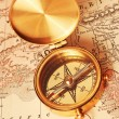 Antique brass compass over old map — Stockfoto