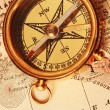 Stock Photo: Antique brass compass over old map