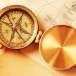 Antique brass compass over old map — Stock Photo #1595429