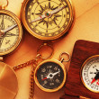 Four antique compasses over old backgrou — Stock Photo