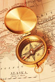 Antique brass compass over old map — ストック写真