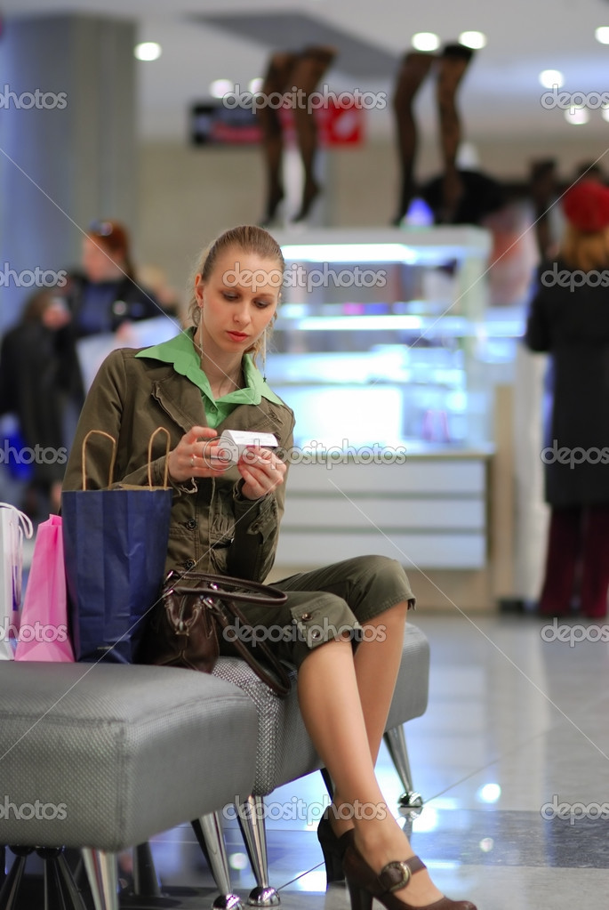 Girl is examining the bill in shopping mall. Shallow depth of field.                                     — Stock Photo #1595295