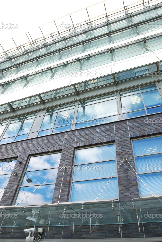 Modern office building with sky reflection in windows — Stock Photo #1705849