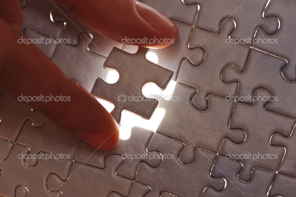 Hand placing missing puzzle piece with shallow DOF — Stock Photo #1810113