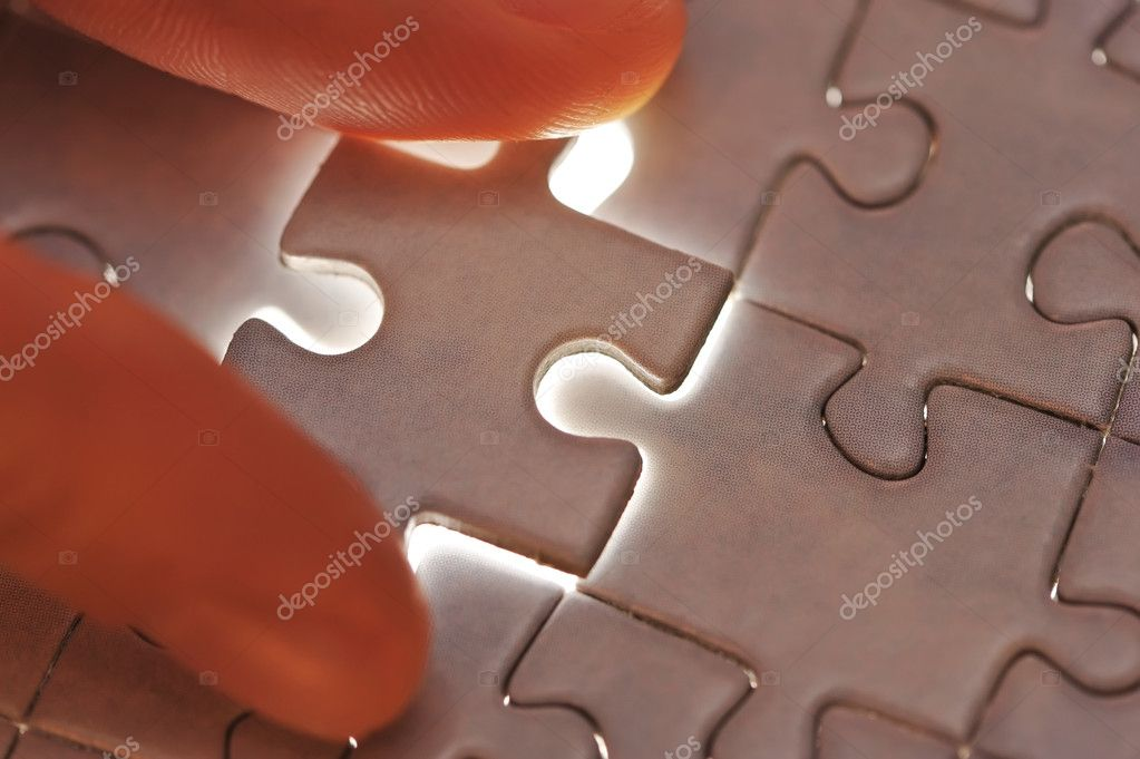 Hand placing missing puzzle piece with shallow DOF — Stock Photo #1826241