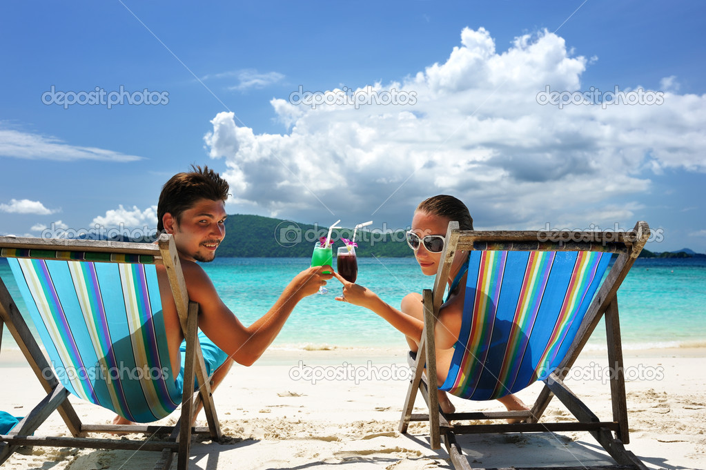 Couple on a tropical beach in chaise lounge  Stock Photo #2124382