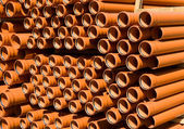 Stacked PVC orange pipes — Stock Photo
