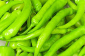 Many green hot peppers arranged at the m — Stock Photo