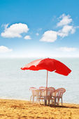 Table, chairs and parasol on the beach — Stock Photo