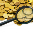 Magnifying glass and lots of gold coins - Stock Photo