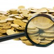 Magnifying glass and lots of gold coins — Stockfoto