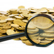 Magnifying glass and lots of gold coins — Stock Photo