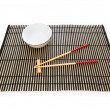 Chopsticks and plate on the bamboo mat — Stock Photo