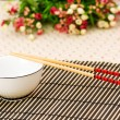 Chopsticks and bowl on the bamboo mat — Stock Photo #1636519