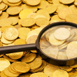 Magnifying glass and gold coins - Stock Photo