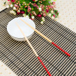 Stock Photo: Chopsticks and bowl on the bamboo mat