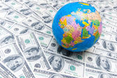 Globe over many dollar bank notes — Stock Photo