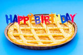 Happy birthday candles in the pie — Stock Photo