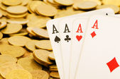 Four aces and lots of gold coins — Stock Photo