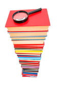 Magnifying glass over the stack of books — Stock Photo