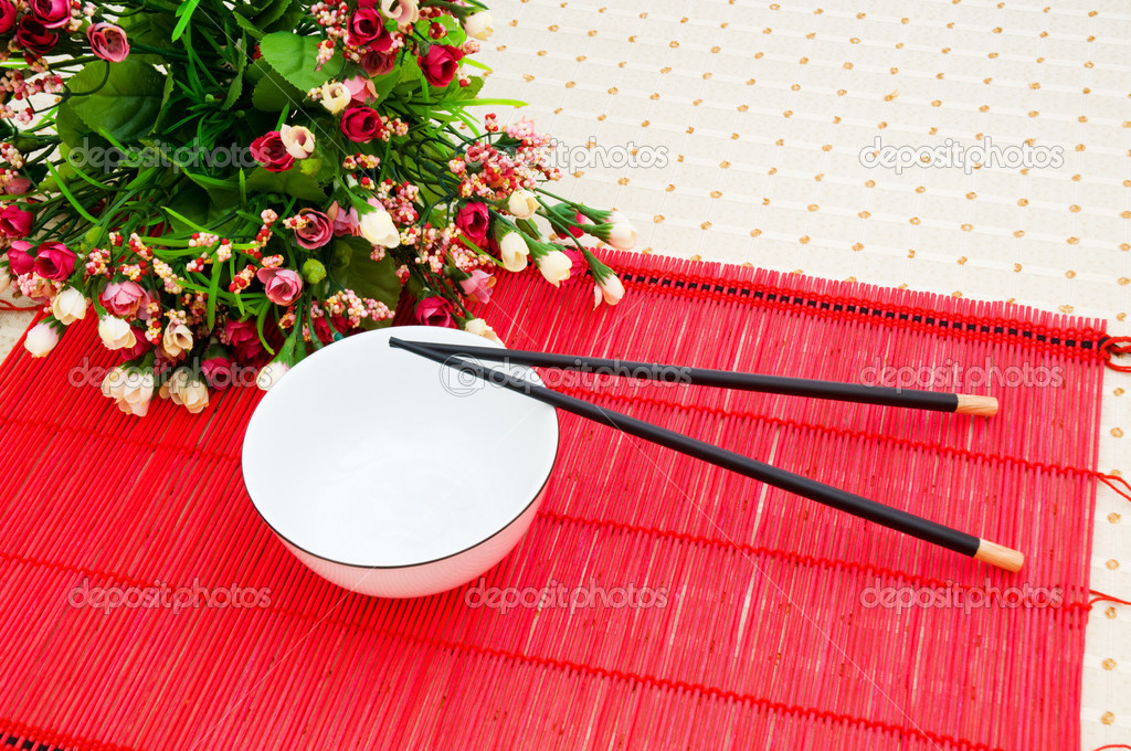 Chopsticks and bowl on the bamboo mat — Stock Photo #1925871