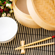 Chopsticks and bowl on the bamboo mat — Stock Photo #1936589