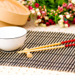Chopsticks and bowl on the bamboo mat — Stock Photo #1937171