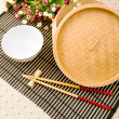 Chopsticks and bowl on the bamboo mat — Stock Photo #1937172