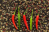Red and green peppers on pepper — Stock Photo