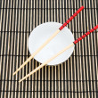 Chopsticks and bowl on the bamboo mat — Stock Photo #1940618