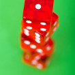 Red dice against green background — Stock Photo