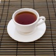 Stock Photo: Cup of teon striped mat