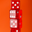 Royalty-Free Stock Photo: Red dice stack against orange