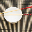 Chopsticks and bowl on the bamboo mat — Stock Photo