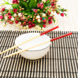 Chopsticks and bowl on the bamboo mat — Stock Photo #1944664