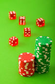 Casino chips and dice against green — Stock Photo
