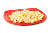 Popcorn on red plate isolated on white — Stock Photo