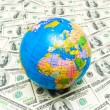 Globe over many american dollars — Stock Photo
