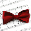 Red bow tie on musical notes - Stock Photo