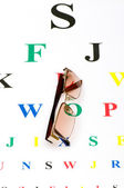 Optical glasses over the eye test table — Stock Photo