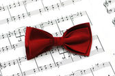 Red bow tie on musical notes — Stock Photo