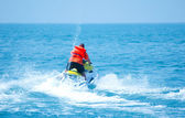 Man driving a motorised scooter at sea — Stock Photo