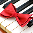 Stock Photo: Red bow tie on piano keys