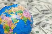 Globe isolated on background of dollars — Stock Photo