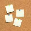 Yellow post it notes on the corkboard - Stock Photo