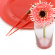 Red flower and plate with chopsticks — Stock Photo